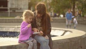 A mamã e a filha jogam no app no telefone na fonte no por do sol filme