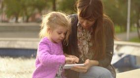 A mamã e a filha jogam no app no telefone na fonte no por do sol video estoque
