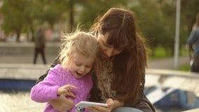 A mamã e a filha jogam no app no telefone na fonte no por do sol vídeos de arquivo