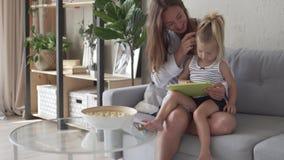 A mamã e a filha jogam um jogo educacional em uma tabuleta em casa vídeos de arquivo