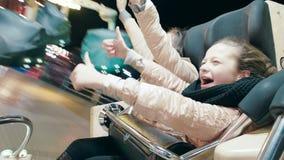 A mamã e a filha montam em uma atração de giro na noite em um parque de diversões video estoque