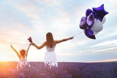 A mamã e a filha na alfazema colocam no por do sol Conceito do amor da família imagem de stock