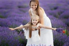 Mamã e filha no campo da alfazema Conceito do amor da família Mosca da menina nas mãos das mães fotografia de stock