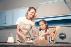 Mamã e filha no cozinheiro Mafins da cozinha Uma filha guarda um ovo da galinha em sua mão que adicionará à farinha foto de stock royalty free