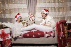 Mamã e filha no sofá com presentes Fotografia de Stock Royalty Free