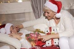 Mamã e filha no sofá com presentes Fotos de Stock Royalty Free