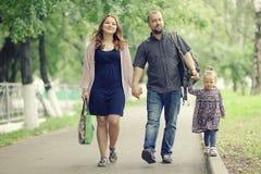 A mamã e a filha nova e o paizinho que andam no verão estacionam Imagens de Stock Royalty Free