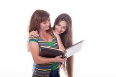 A mamã e a filha olham um álbum de fotografias, leram um livro Foto de família Emoções diferentes Imagens de Stock Royalty Free