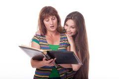 A mamã e a filha olham um álbum de fotografias, leram um livro Foto de família Emoções diferentes Imagem de Stock