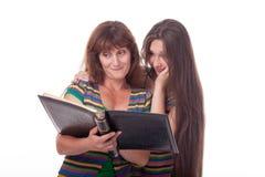 A mamã e a filha olham um álbum de fotografias, leram um livro Foto de família Emoções diferentes Imagem de Stock Royalty Free