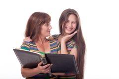 A mamã e a filha olham um álbum de fotografias, leram um livro Foto de família Emoções diferentes Fotografia de Stock Royalty Free
