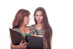 A mamã e a filha olham um álbum de fotografias, leram um livro Foto de família Emoções diferentes Foto de Stock
