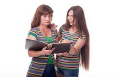 A mamã e a filha olham um álbum de fotografias, leram um livro Foto de família Emoções diferentes Foto de Stock Royalty Free