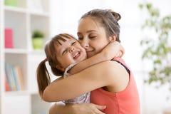 Mamã e filha que abraçam em casa imagens de stock royalty free
