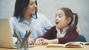 Mamã e filha que abraçam-se que olha um portátil cinzento na tabela Durante este fundo borrado O conceito de vídeos de arquivo