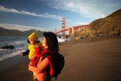 Mamã e filha que apreciam o por do sol na porta dourada Fotografia de Stock