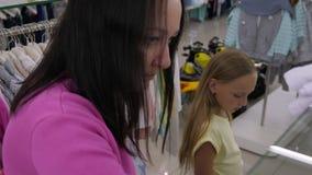 Mamã e filha que escolhem a roupa durante a compra no boutique moderno video estoque