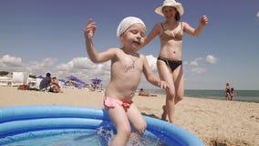 Mamã e filha que têm o divertimento junto na associação na praia no dia ensolarado vídeos de arquivo