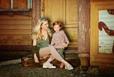 A mamã e a filha ruivo são de assento e de sorriso nas etapas imagem de stock