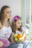 A mamã e a filha sentam-se perto da janela Foto de Stock Royalty Free