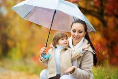 A mamã e a filha sob o guarda-chuva escondem da chuva Fotografia de Stock Royalty Free