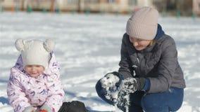 A mamã e a filha têm o divertimento na rua em um dia nevado do inverno bonito, minha neve dos lances da mãe na menina, menina filme