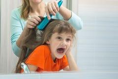 A mamã e a filha tiverem o divertimento quando mum que penteia o cabelo dos childs Foto de Stock