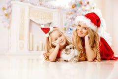 A mamã e a filha vestidas como Santa comemoram o Natal Família em Fotografia de Stock