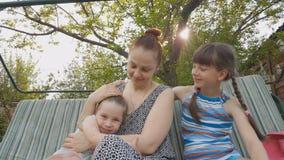 Mamã e filhas que sentam-se em um balanço do jardim, em relações de família dos pais e em crianças video estoque