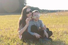 Mamã e filho bolhas de sabão de sopro que sentam-se na grama, fim de semana da família no parque foto de stock