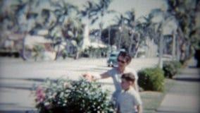 1959: Mamã e filho da rua alinhada árvore como passagens clássicas velhas do carro Miami, florida video estoque