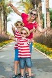Mamã e filho dois nos óculos de sol e nos chapéus a andar através da aleia das palmeiras Férias de verão da família foto de stock
