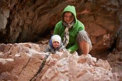 Mamã e filho pequeno que sentam-se na rocha fotos de stock