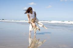 Mamã e filho que andam em uma praia Imagens de Stock Royalty Free