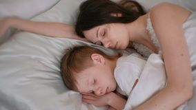 Mamã e filho que dormem junto Mamã que abraça seu filho vídeos de arquivo