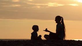 Mamã e filho que jogam na praia com pedras Tempo do por do sol, silhuetas video estoque