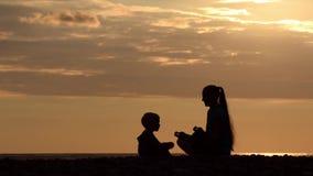 Mamã e filho que jogam na praia e nos asanas do estudo Tempo do por do sol, silhuetas video estoque
