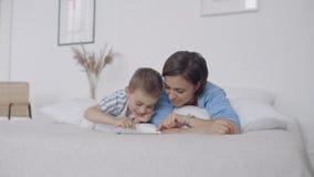 Mamã e filho que olham a tela da tabuleta que encontra-se em uma cama branca Jogos do jogo com seu filho em seu tablet pc e video estoque