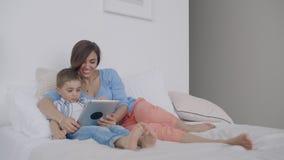 Mamã e filho que olham a tela da tabuleta que encontra-se em uma cama branca Jogos do jogo com seu filho em seu tablet pc e filme