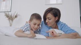 Mamã e filho que olham a tela da tabuleta que encontra-se em uma cama branca Jogos do jogo com seu filho em seu tablet pc e vídeos de arquivo