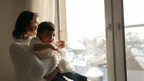 Mamã e filho que sentam-se na janela grande da casa no inverno video estoque