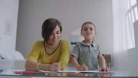 Mamã e filho que sentam-se na tabela do espelho na tração da sala branca com os lápis coloridos que sorriem e que riem video estoque