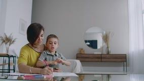Mamã e filho que sentam-se na tabela do espelho na tração da sala branca com os lápis coloridos que sorriem e que riem vídeos de arquivo