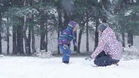 Mamã e filho que têm a parte externa do divertimento em uma floresta ou em um parque em um dia nevado do inverno bonito durante u filme