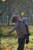 A mamã e o bebê em um estilingue exultam as folhas de outono de queda Fotografia de Stock Royalty Free