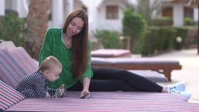 A mamã e o bebê estão olhando entusiasticamente vídeos em um smartphone em um vadio filme