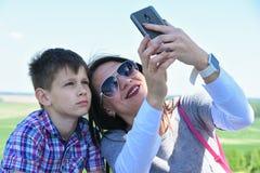 A mamã e o filho da família fazem o selfie na natureza no verão Fotos de Stock Royalty Free