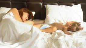 A mamã e o filho dormem na manhã na cama em filme