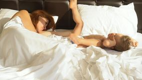 A mamã e o filho dormem na manhã na cama em vídeos de arquivo