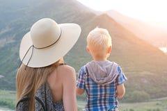 A mamã e o filho estão com suas partes traseiras na perspectiva das montanhas verdes Imagem de Stock